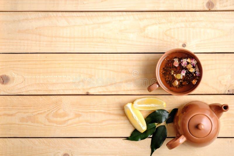 Ajuste de la ceremonia de té en fondo de madera, la taza de té, la tetera, el limón y las hojas verdes Visión superior, composici imágenes de archivo libres de regalías