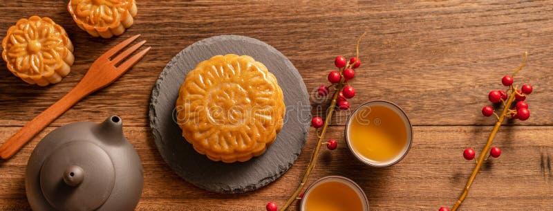 Ajuste de la tabla del Mooncake de la torta de la luna - pasteles tradicionales chinos con las tazas de té en el fondo de madera, imagenes de archivo