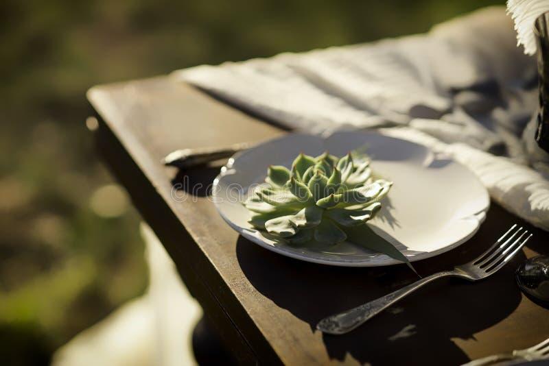 Ajuste de la tabla del vintage con la flor en una placa en una tabla de madera Decoración rústica de la boda del estilo fotos de archivo libres de regalías