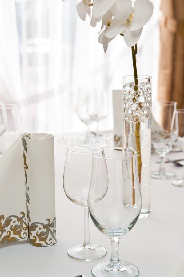 Ajuste de la tabla en restaurante con la flor de la orquídea imagenes de archivo