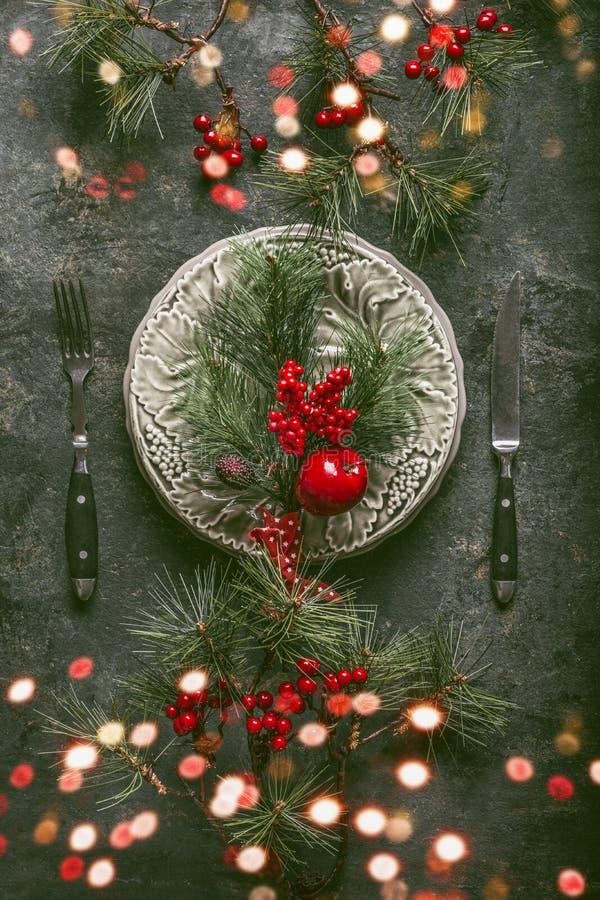 Ajuste de la tabla de la Navidad con el bokeh para la cena del día de fiesta con la placa, los cubiertos, las ramas del abeto y l foto de archivo libre de regalías