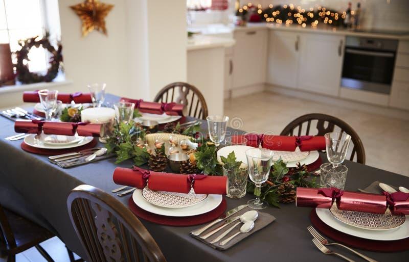 Ajuste de la tabla de la Navidad con las galletas de la Navidad dispuestas en las placas en un comedor, con la cocina en el fondo imagen de archivo