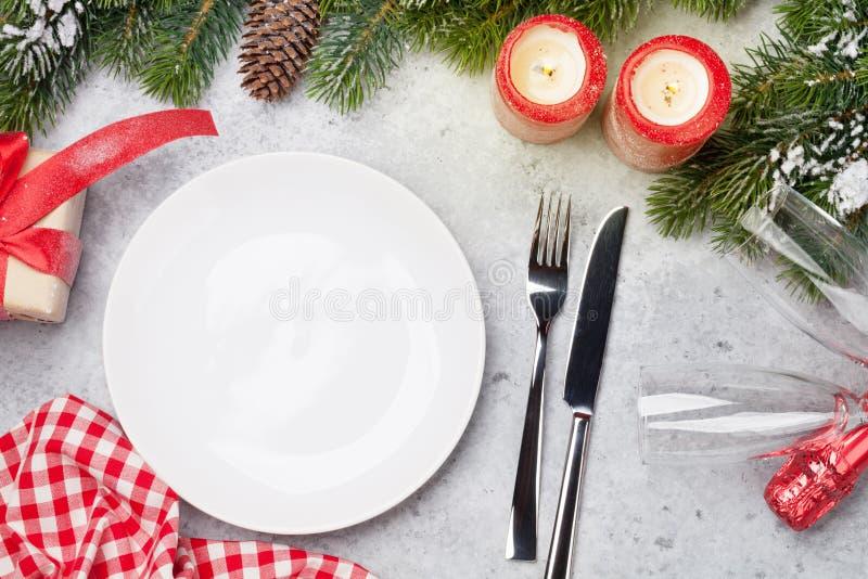 Ajuste de la tabla de la Navidad con las velas, el champán, la caja de regalo y la rama de árbol de abeto cubiertos por la nieve  foto de archivo