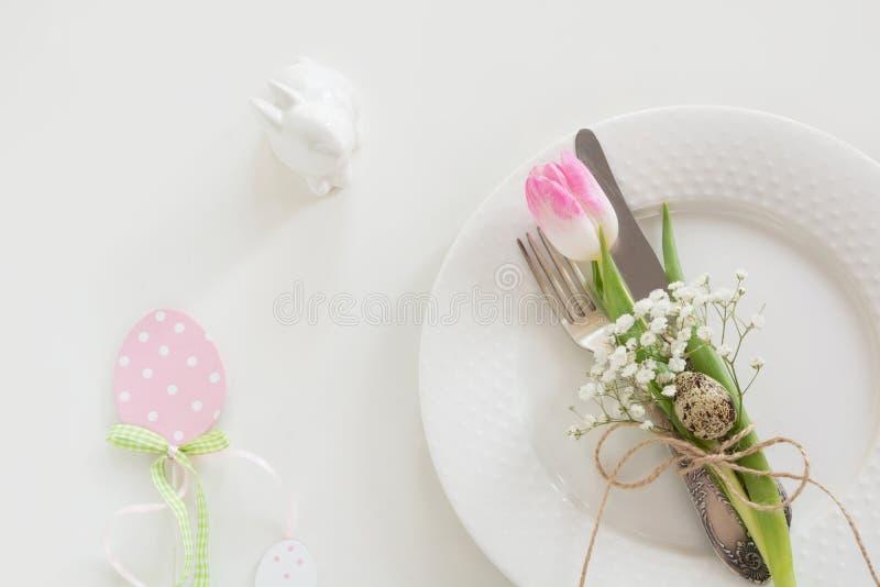 Ajuste de la tabla de Pascua con la cinta rosada y tulipán en el fondo blanco Cena de la primavera Espacio de la visión superior  fotografía de archivo