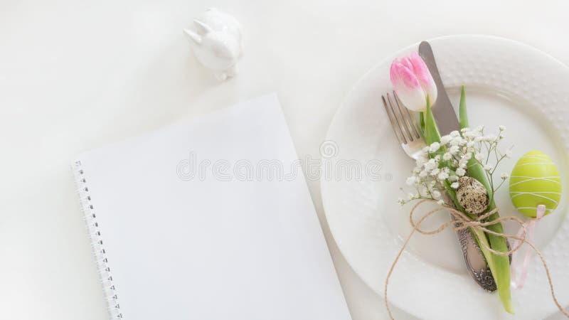 Ajuste de la tabla de Pascua con la decoración y nota vacía sobre el fondo blanco Cena romántica de la primavera Espacio de la vi fotos de archivo libres de regalías