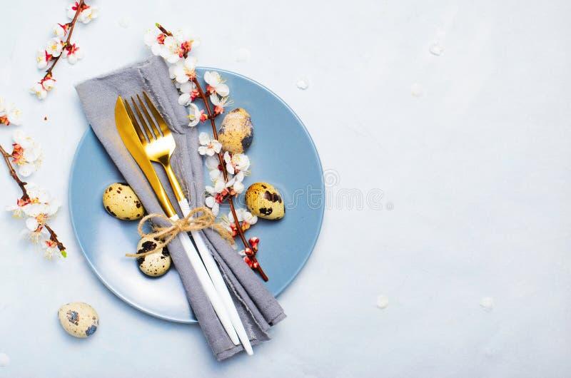 Ajuste de la tabla de Pascua con los huevos y las ramas de codornices en el flor, fondo de los d?as de fiesta de la primavera foto de archivo