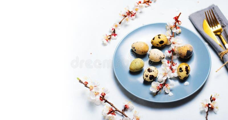 Ajuste de la tabla de Pascua con los huevos y las ramas de codornices en el flor, fondo de los d?as de fiesta de la primavera imagen de archivo