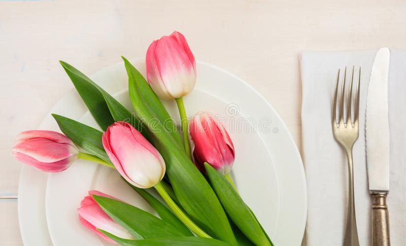 Ajuste de la tabla de la primavera con los tulipanes rosados en el fondo de madera blanco Visión superior imagen de archivo libre de regalías