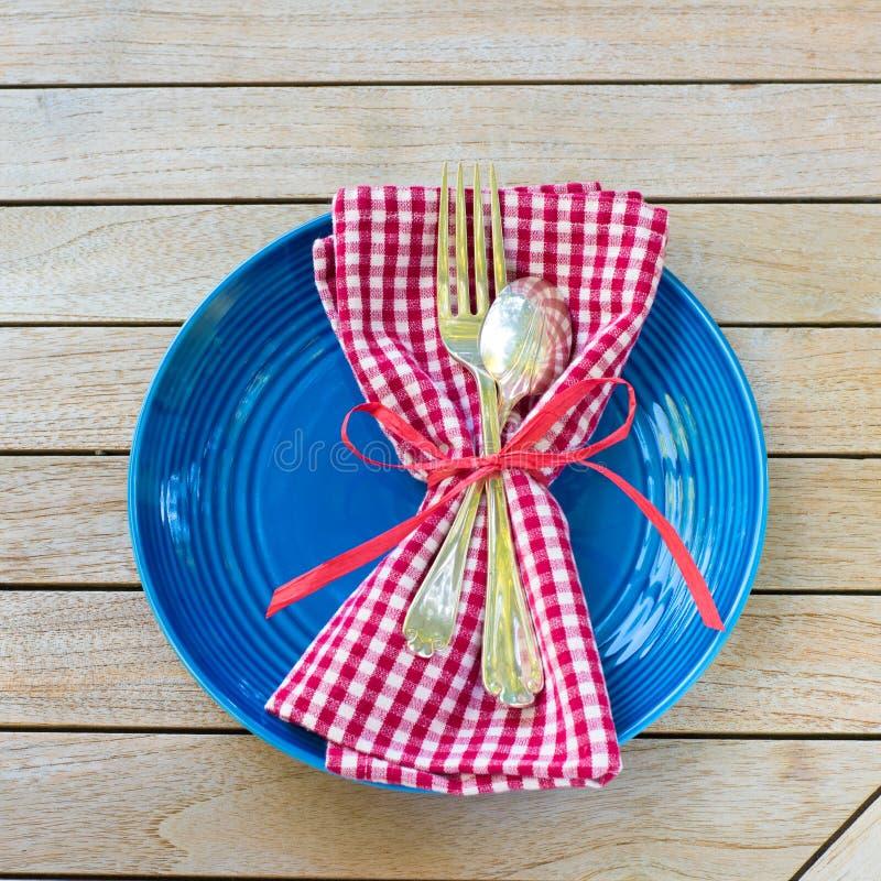 Ajuste de lugar branco e azul vermelho da tabela de piquenique com guardanapo, forquilha, colher e placa Outsid tomado do estilo  fotos de stock