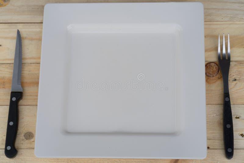 Ajuste de lugar com placa, faca, forquilha e colher no branco imagens de stock