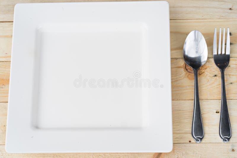 Ajuste de lugar com placa, forquilha e colher no branco imagem de stock