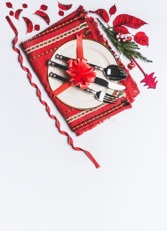 Ajuste de lugar festivo da tabela do Natal com tabela-guardanapo vermelho, cutelaria, placa, curva vermelha grande, de árvore de  imagem de stock