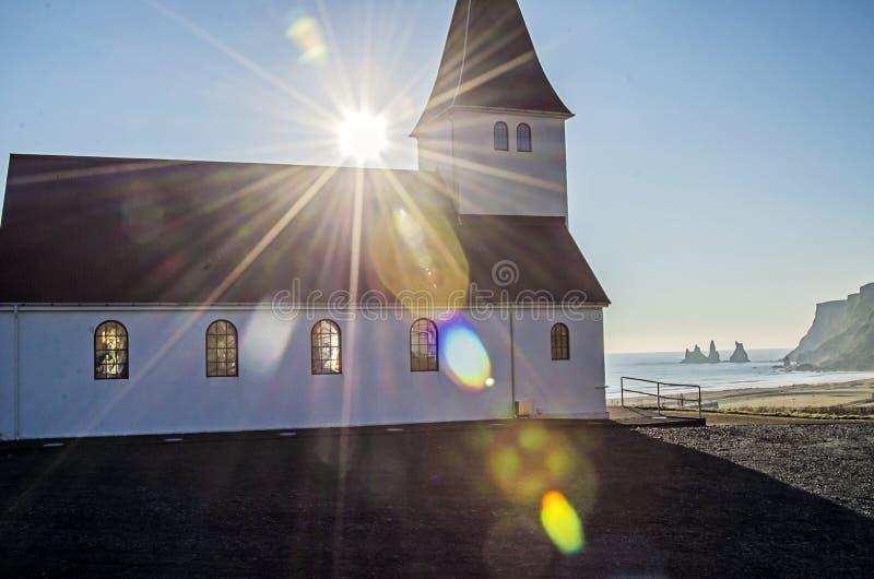 Ajuste de Sun atrás da igreja em Vik Iceland fotos de stock royalty free