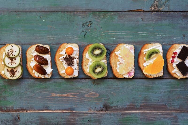 Ajuste de uma variedade de sanduíches doces em um fundo de madeira verde da prancha Vista superior, lugar para o texto fotos de stock