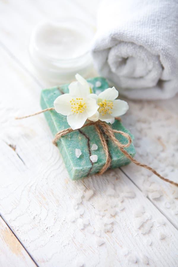 Ajuste del balneario con el flor del jazmín, el jabón hecho a mano natural y la sal del mar en la tabla de madera blanca fotos de archivo libres de regalías