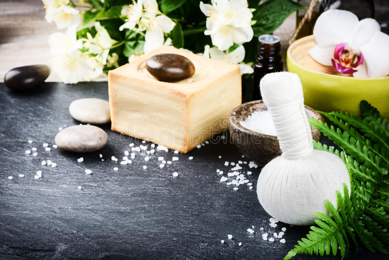 Ajuste del balneario con la bola herbaria del masaje, las flores y el aceite esencial imagen de archivo
