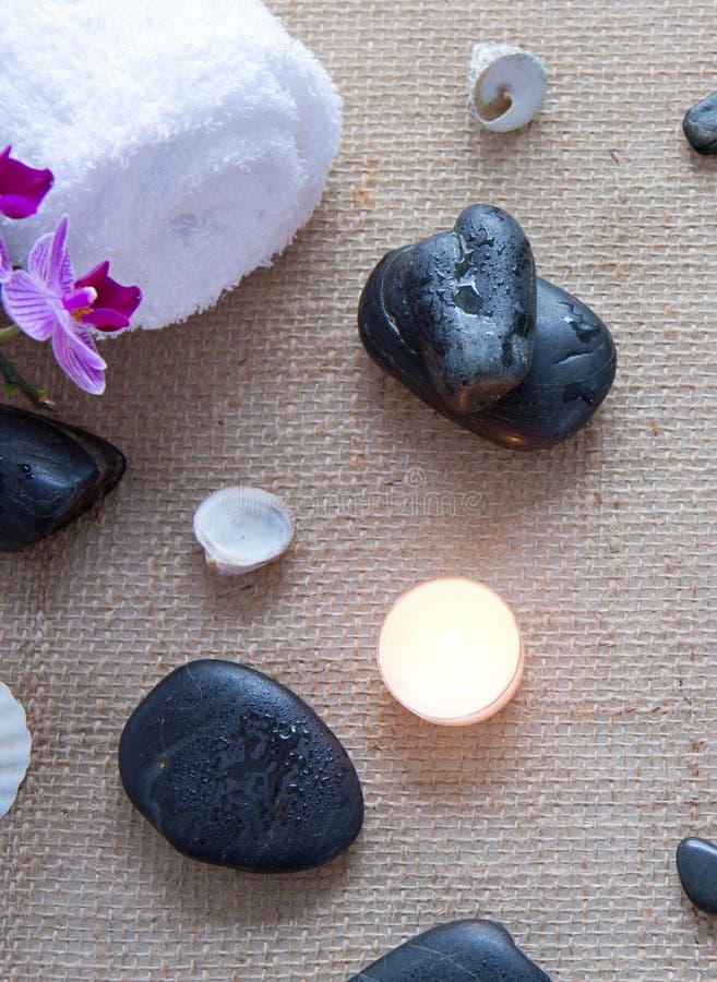 Ajuste del balneario con la flor, las piedras y la toalla de la orqu?dea en un fondo del pa?o fotografía de archivo
