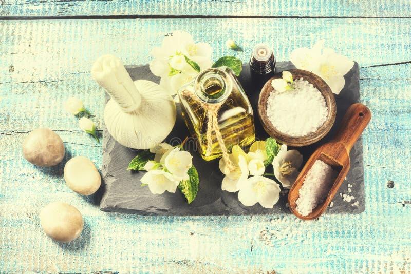 Ajuste del balneario con las flores del jazmín y el aceite esencial sobre azul viejo foto de archivo