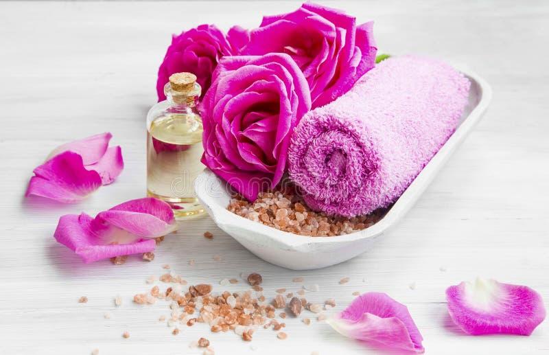 Ajuste del balneario con las rosas, la sal de baño y el aceite, toalla del algodón foto de archivo libre de regalías
