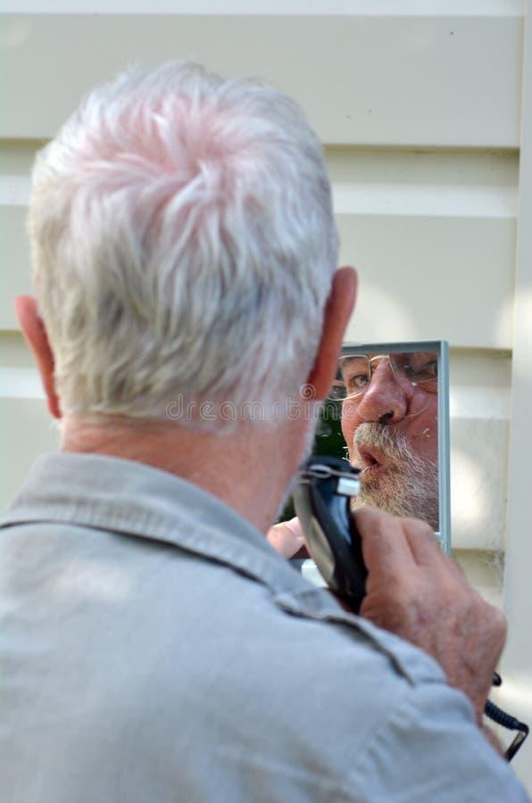 Ajuste del hombre su barba fotografía de archivo libre de regalías