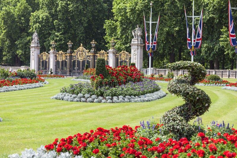 Ajuste delante del Buckingham Palace con el macizo de flores y la puerta decorativa para poner verde el parque, Londres, Reino Un fotografía de archivo