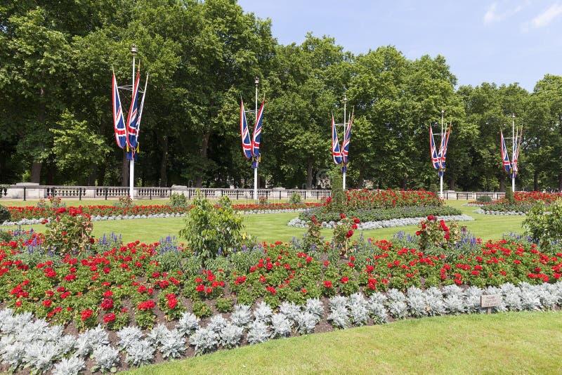 Ajuste delante del Buckingham Palace con el macizo de flores y la puerta decorativa para poner verde el parque, Londres, Reino Un imagenes de archivo
