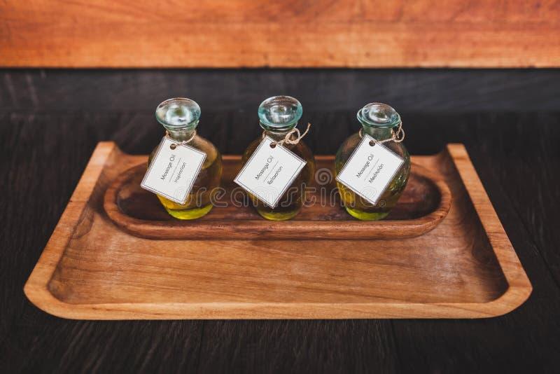 Ajuste do óleo da massagem na placa de madeira em termas tropicais imagem de stock royalty free