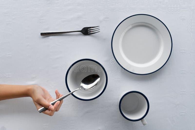 Ajuste do copo branco da bacia do prato na mesa de jantar do alimento com forquilha e na mão que guarda a colher do metal no fund imagens de stock