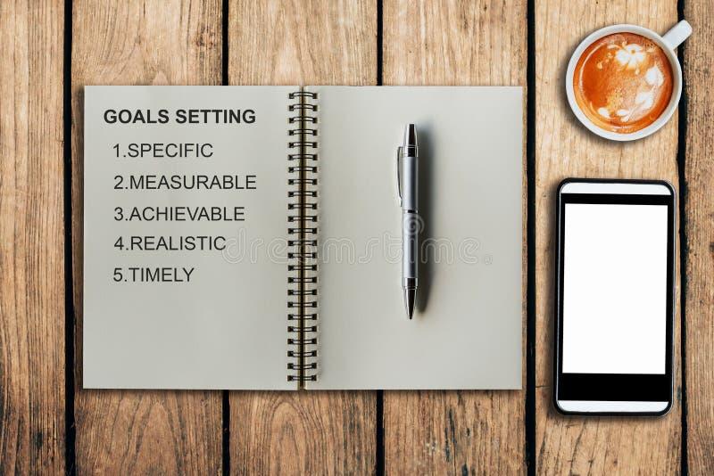Ajuste do objetivo como o memorando no copo do caderno e de café com phon móvel foto de stock