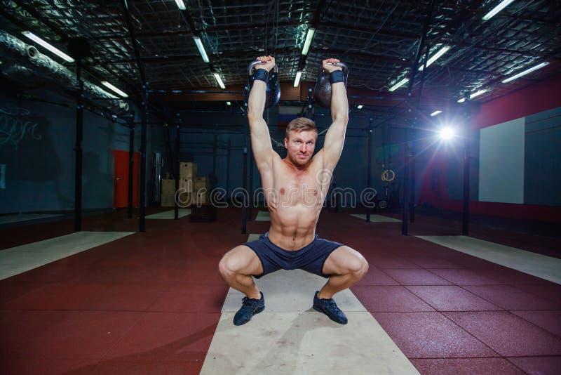 Ajuste do treinamento transversal Homem da aptidão que faz um treinamento do peso levantando o kettlebell Atleta novo que faz bal foto de stock