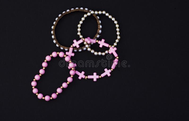 Ajuste dos braceletes bonitos das mulheres no fundo preto com espaço da cópia imagens de stock