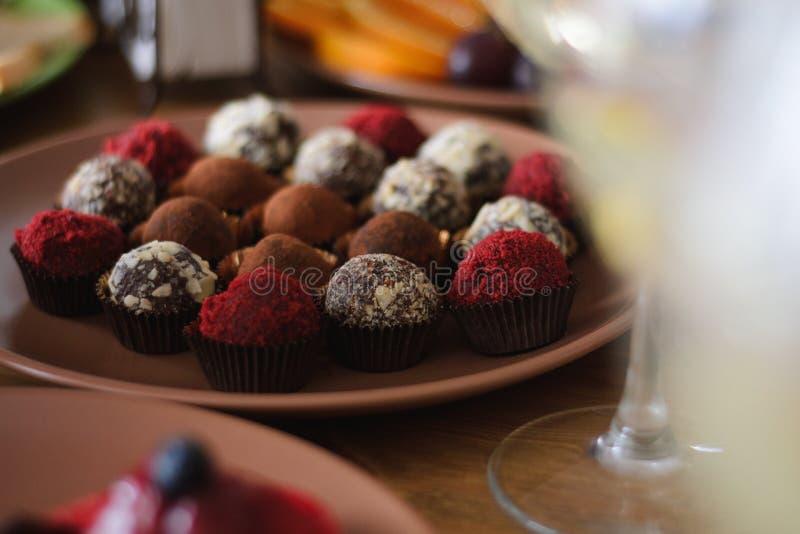 Ajuste dos chocolates deliciosos da trufa na tabela do feriado foto de stock