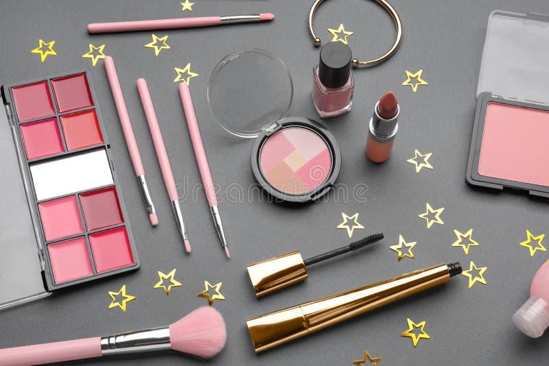 Ajuste dos cosméticos e dos acessórios decorativos no fundo cinzento imagem de stock