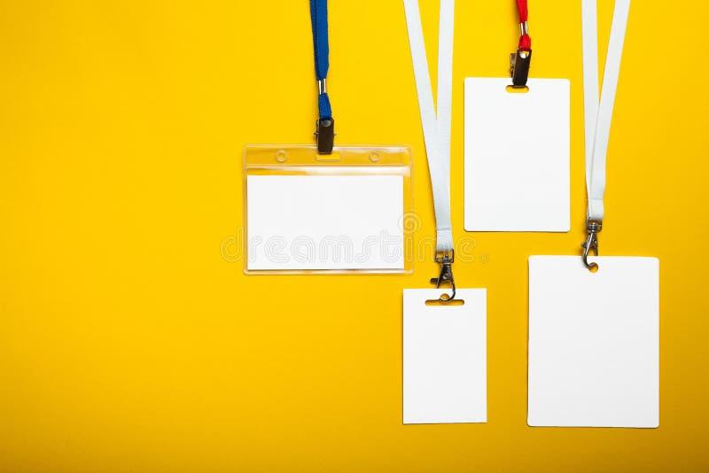 Ajuste dos crachás do cartão com cordas no fundo amarelo Modelo foto de stock