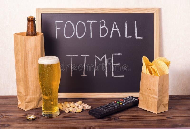Ajuste dos fan de futebol da garrafa de cerveja no saco de papel marrom, vidro, fotografia de stock royalty free
