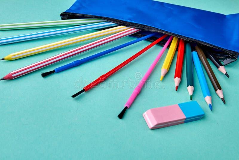 Ajuste dos lápis coloridos dispersados no fundo da cor fotos de stock