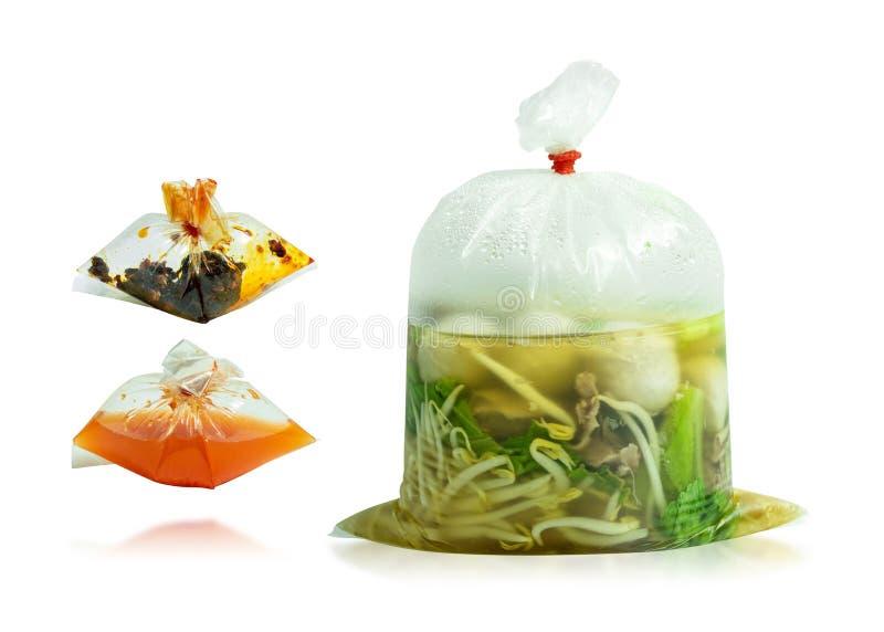 Ajuste dos macarronetes no saco de plástico com o condimento isolado no fundo branco Trajeto de grampeamento imagem de stock