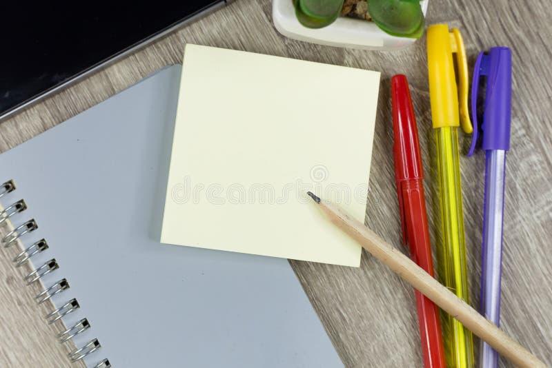 Ajuste dos materiais de escritório para o trabalho com o fundo de madeira da textura foto de stock