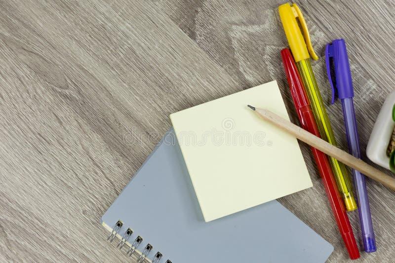 Ajuste dos materiais de escritório para o trabalho com o fundo de madeira da textura fotografia de stock