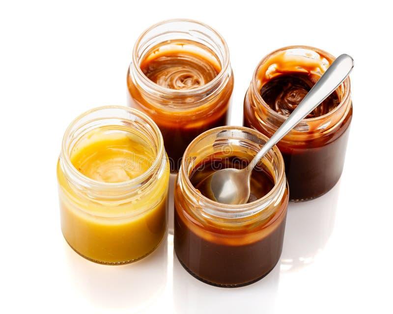 Ajuste dos molhos caseiros do caramelo em uns frascos isolados no fundo branco foto de stock royalty free