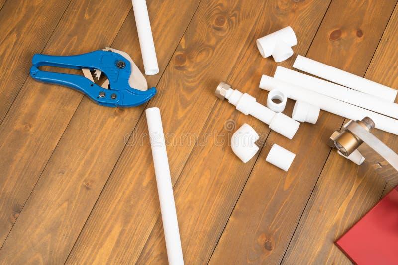 Ajuste dos objetos e das ferramentas para montar as tubulações de água em um fundo de madeira do assoalho imagens de stock