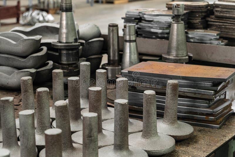 Ajuste dos produtos e dos boletos do ferro fundido e do aço na tabela de aço na loja da planta industrial fotografia de stock royalty free