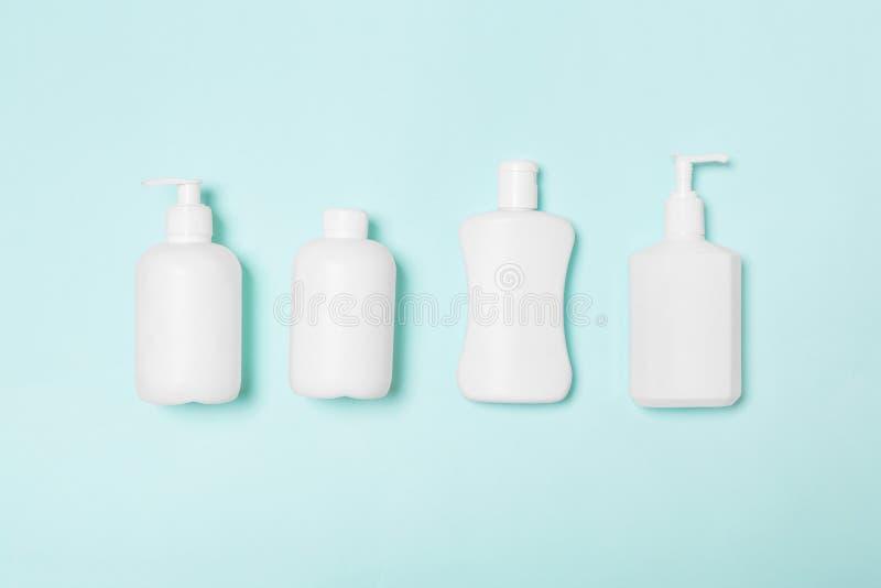 Ajuste dos recipientes cosméticos brancos isolados no fundo azul, vista superior com espaço da cópia Grupo de garrafa plástica do fotografia de stock