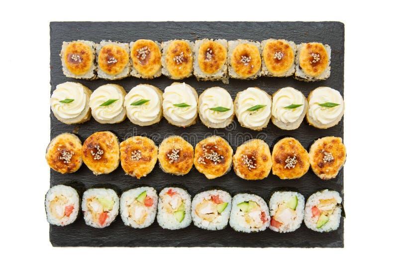 Ajuste dos rolos de sushi japoneses do maki quente da lava isolados na placa do alimento do xisto no fundo branco imagem de stock royalty free