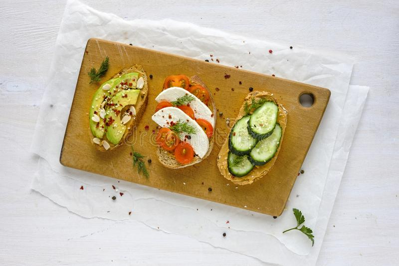 Ajuste dos sanduíches servidos na placa de madeira foto de stock