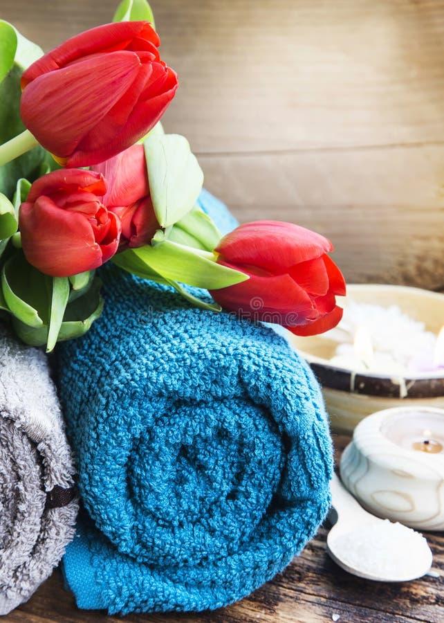 Ajuste dos termas com tulipas vermelhas e as toalhas macias do algodão imagem de stock