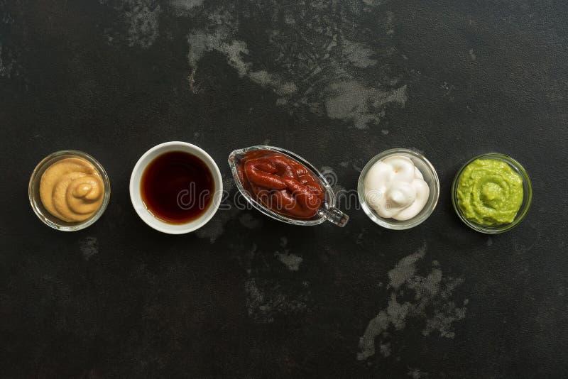 Ajuste dos vários molhos em umas bacias em seguido em um fundo de pedra preto Molho de mostarda, tomate, wasabi, maionese, soja , fotos de stock