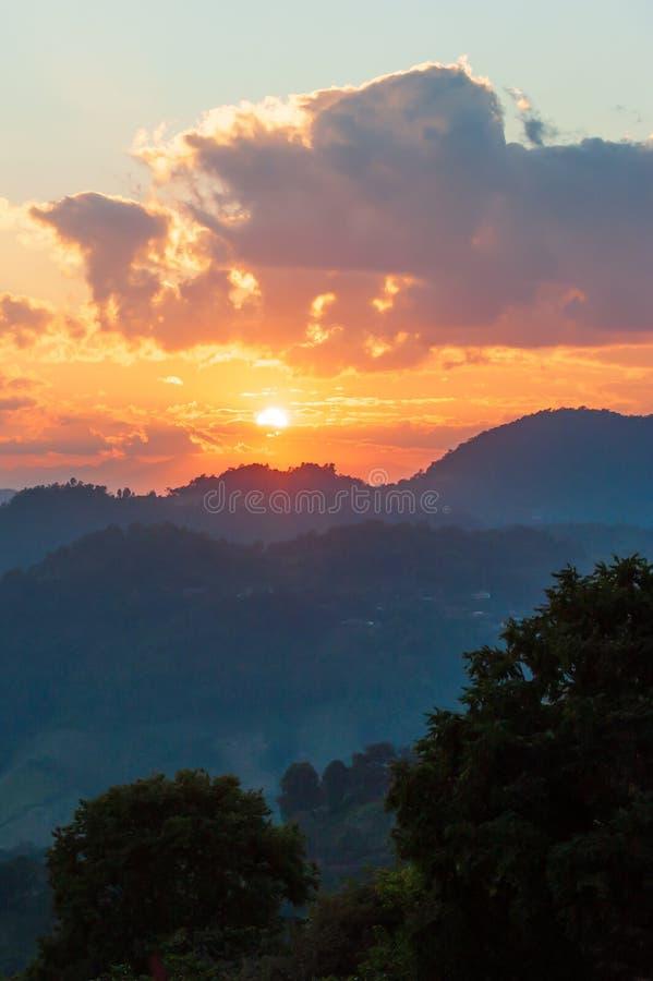 Ajuste dourado do sol sobre a parte superior da montanha de Doi Mae Salong na beira de Tailandês-Myanmar Nuvens e céu fantásticos fotos de stock royalty free