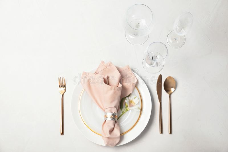 Ajuste festivo da tabela com placas, vidros, cutelaria e guardanapo no fundo claro fotografia de stock