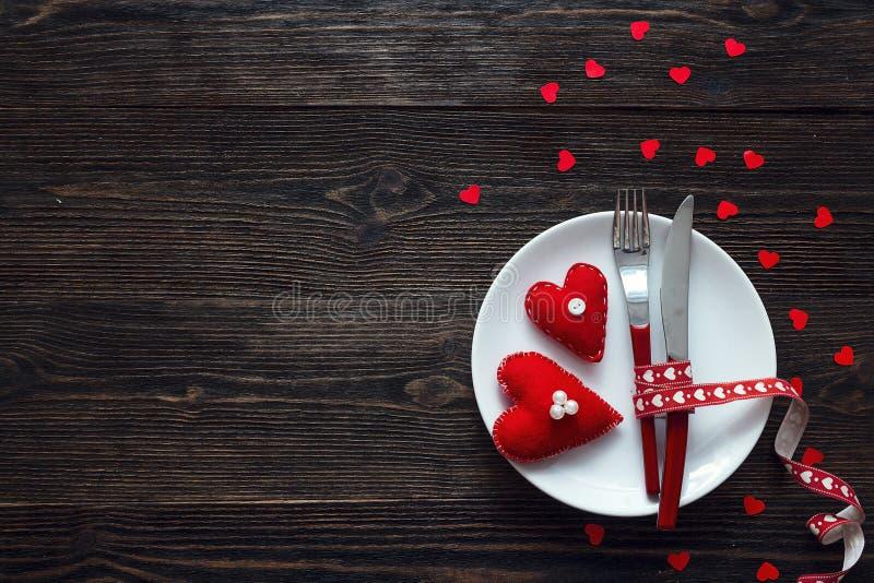 Ajuste festivo de la tabla para el día del ` s de la tarjeta del día de San Valentín con la bifurcación, el cuchillo y h fotos de archivo libres de regalías